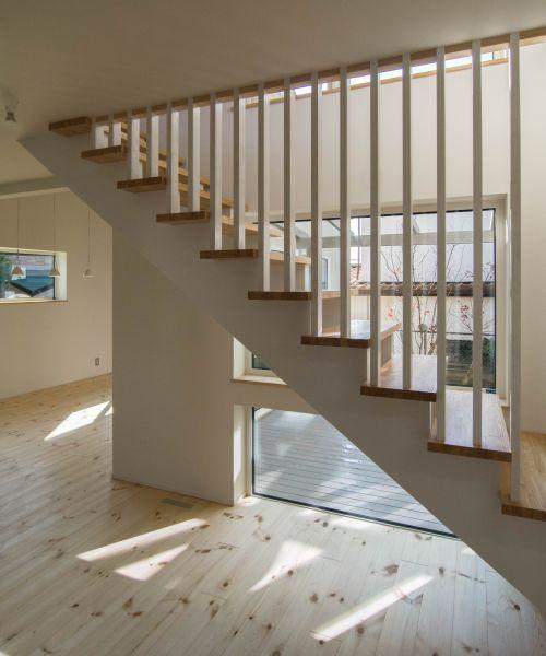 玄関を入った正面で見るパティオに面した2階への階段 ひな壇加工され