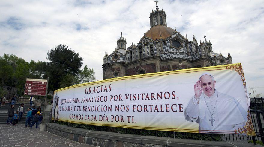 """Una pancarta con la imagen del Papa delante de una capilla """"La Villa"""" de la Basilica Guadalupe."""