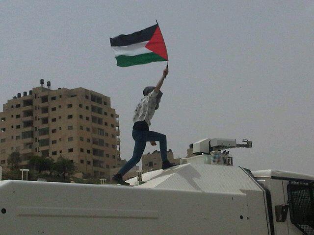 Ativista palestina apoia greve de fome de 3.500 compatriotas subindo a um tanque israelita.