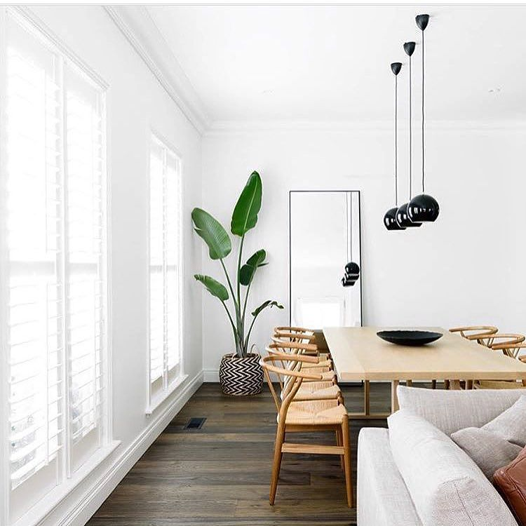 Minimal And Earthy Open Living And Dining Area With White Wood Natural Light Tall Plant Mirror Wicker Dining Room Inspiration Interior Dining Room Design