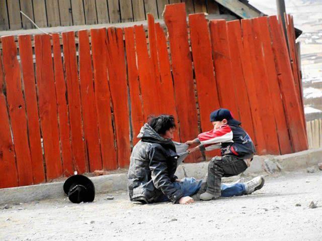 Padre alcohólico con su hijo tratando de levantarlo.