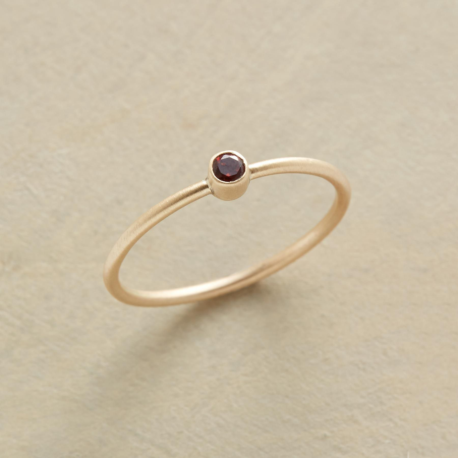 Small wonder ring a dainty drop of red garnet lights up your hand