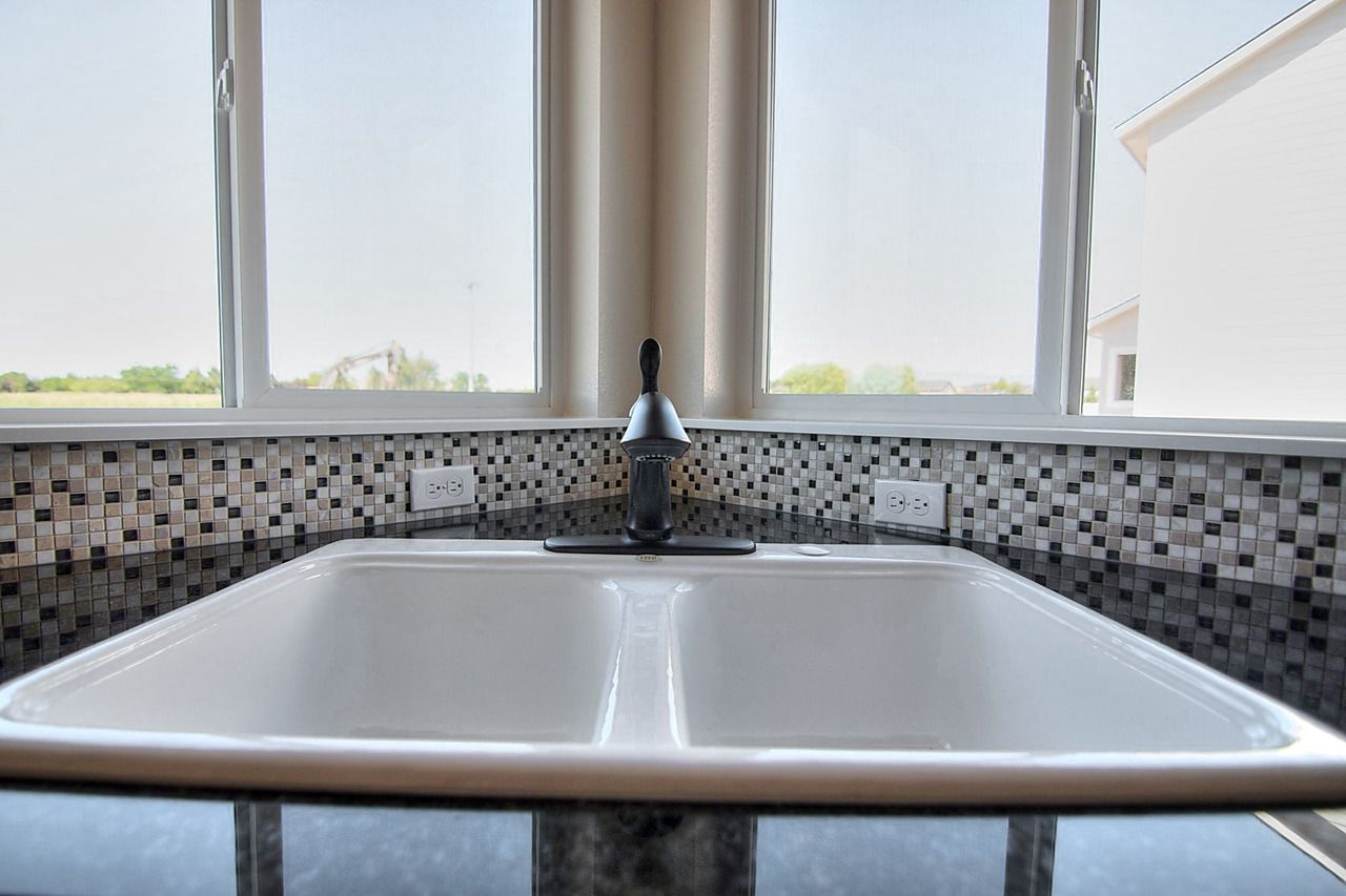 Dishes wouldn't be so bad in this sink! The mosaic backsplash with white grout, white cast iron sink, Linden pull out bronze faucet, and granite counter tops complete the view this view! #shinynewawesome #whitesink #bronzefaucet #granitecountertop