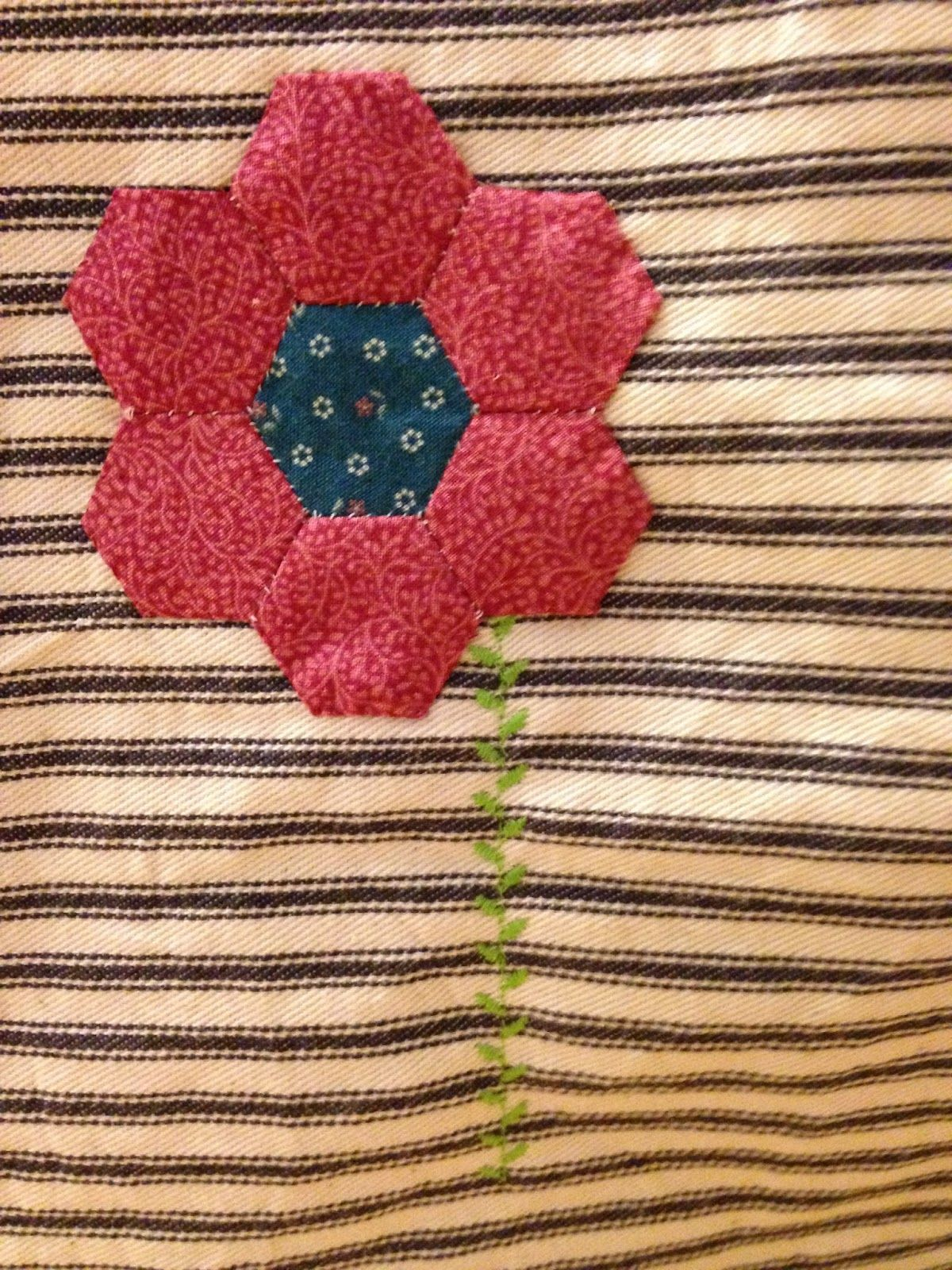 Grandmothers Garden Hexagon is used on the side of a fabric Table