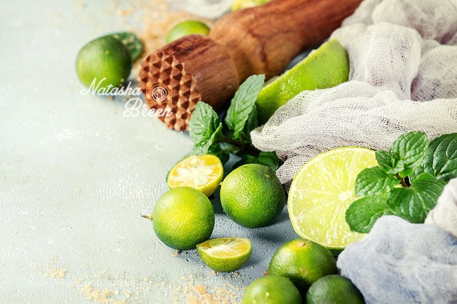 Mojito Ingredients by NatashaBreen from http://500px.com/photo/201830045 - Ingredients for mojito cocktail whole sliced lime and mini limes mint leaves brown crystal sugar over gray stone texture background with gauze textile and wooden bar muddler. Close up space. More on dokonow.com.