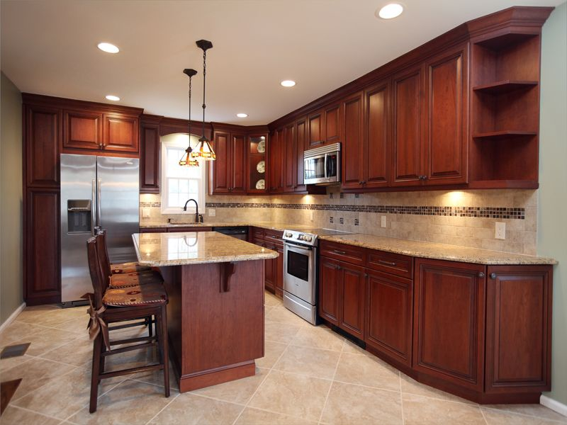 Amber cherry mitred raised kitchen cabinets with a brown for Brown kitchen cabinets with black granite