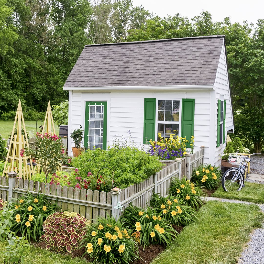 With crisp white siding, Kelly green accents, and a low profile, this garden shed takes its cue from Cape Cod-style homes. #gardensheds #bhg