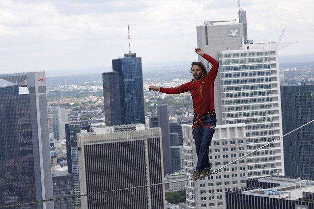 Professional slackliner Reinhard Kleindl walks a high wire in front of the Frankfurt skyline May 25, 2013. Austrian Kleindl set a world record on Saturday by walking the highest urban high line at 607 ft (185 m). (Photo by Ralph Orlowski/Reuters)  http://avaxnews.net/fact/The_Week_in_Pictures_May_26-May_31_2013.html