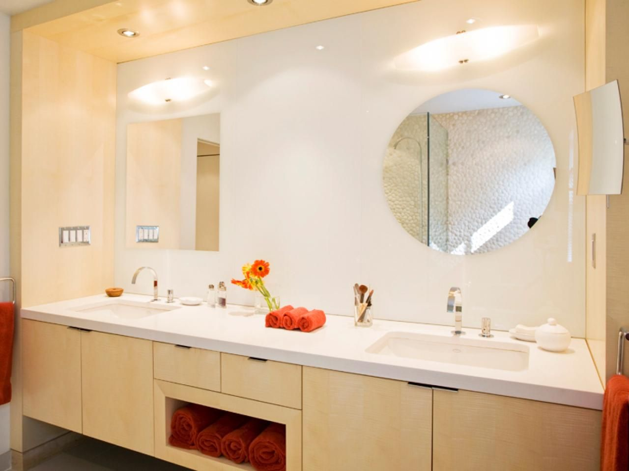 Geometric mirrors adorn this contemporary double vanity bathroom. Coral-colored accents add a pop of color to an otherwise neutral space.