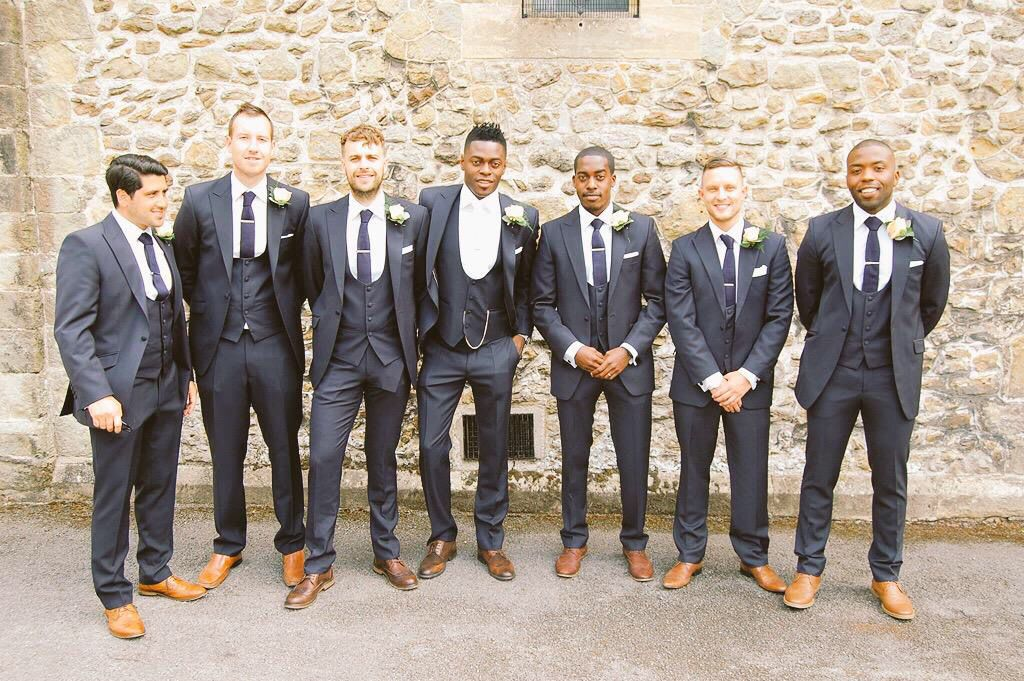 Groom and ushers in navy blue slim fit suits with scoop waistcoats ...