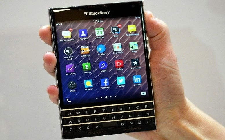 A woman holds the blackberry passport smartphone during at