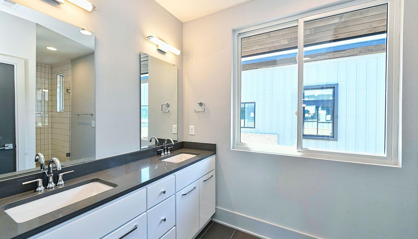 Master Bathroom With Modern Lighting White Slab Cabinetry
