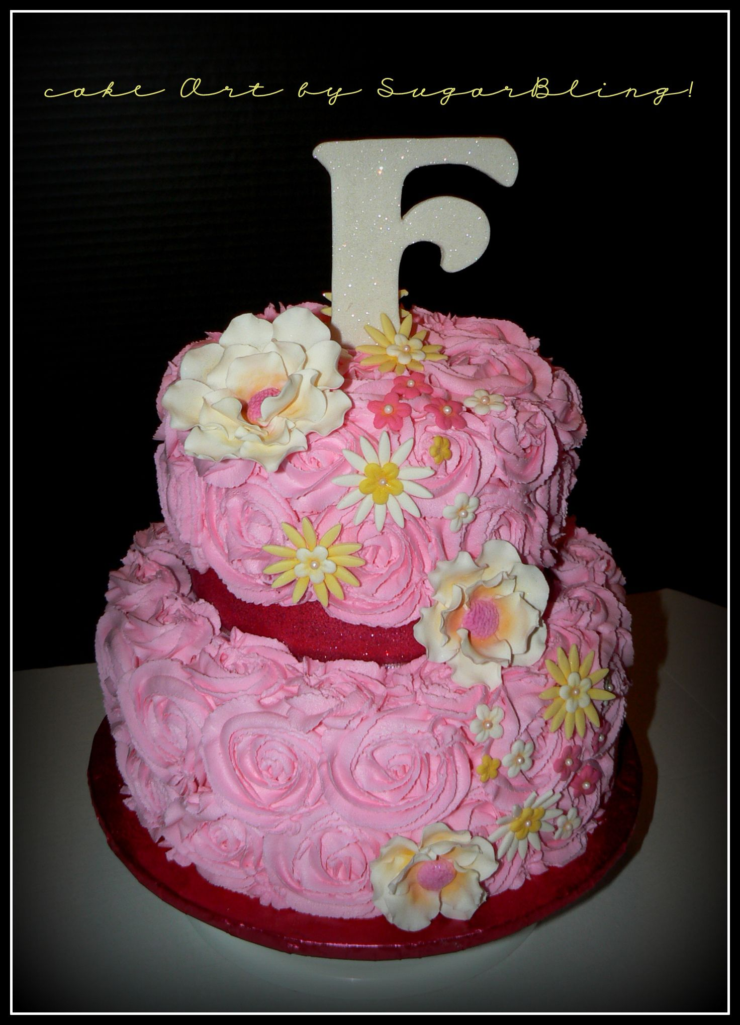 A birthday cake of piped buttercream roses and gumpaste flowers