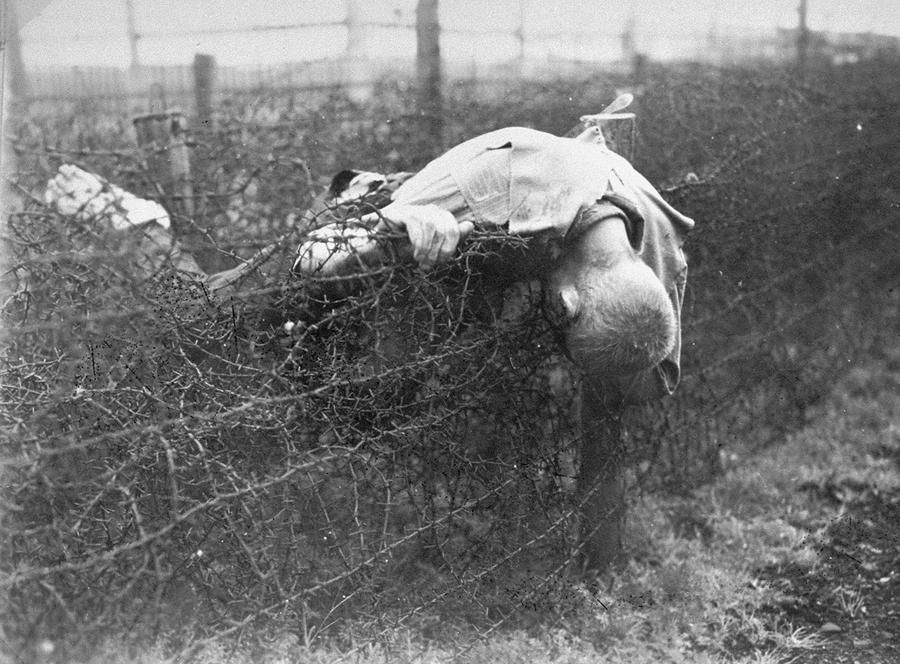 The corpse of a prisoner lies on the barbed wire fence in Leipzig ...