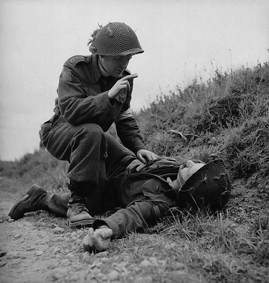 H-Captain Robert Seaborn, Chaplain of the 1st Battalion, The Canadian Scottish Regiment, giving absolution to an unidentified soldier of the 3rd Canadian Infantry Division near Caen, France, 15 July 1944