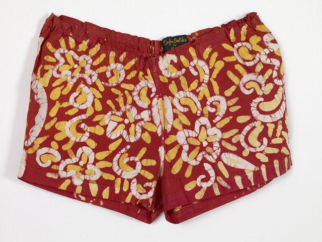 Lyhyet punaiset shortsit on kuvioitu kauttaaltaan sormenpaksuisella viivalla tehdyllä valkoisella ja keltaisella batiikkikuvioinnilla. Kuviot muodostuvat lyhyistä viivoista ja kiemuroista, jotka mu...