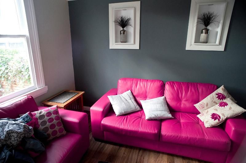 Stylish living room with pink and grey decor with a comfortable ...