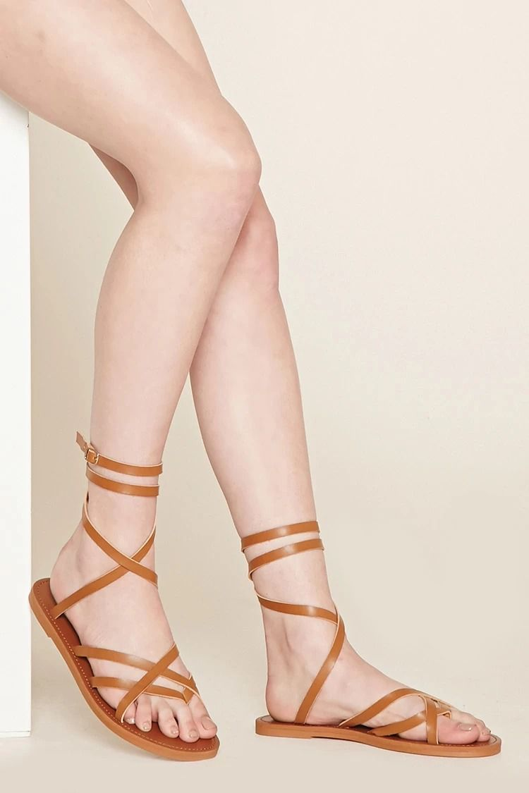 6e93bff8f240 A pair of faux leather sandals featuring a crisscross vamp and crisscross  ankle straps with a buckled closure.  stepitup
