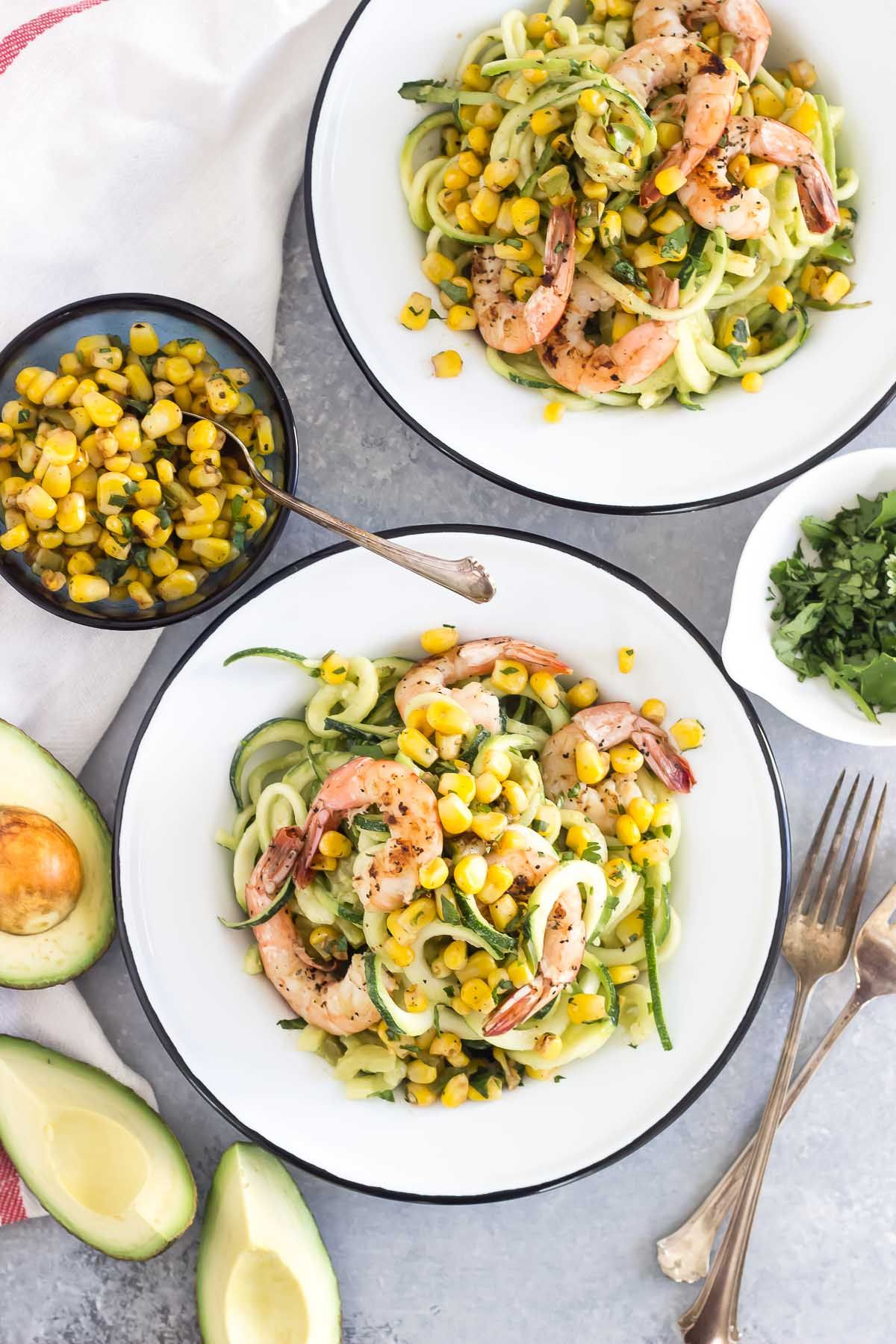 You won't miss the pasta in this spicy avocado zucchini noodle dish! Creamy avocado sauce goes perfectly with spicy grilled shrimp and a sweet corn salsa.