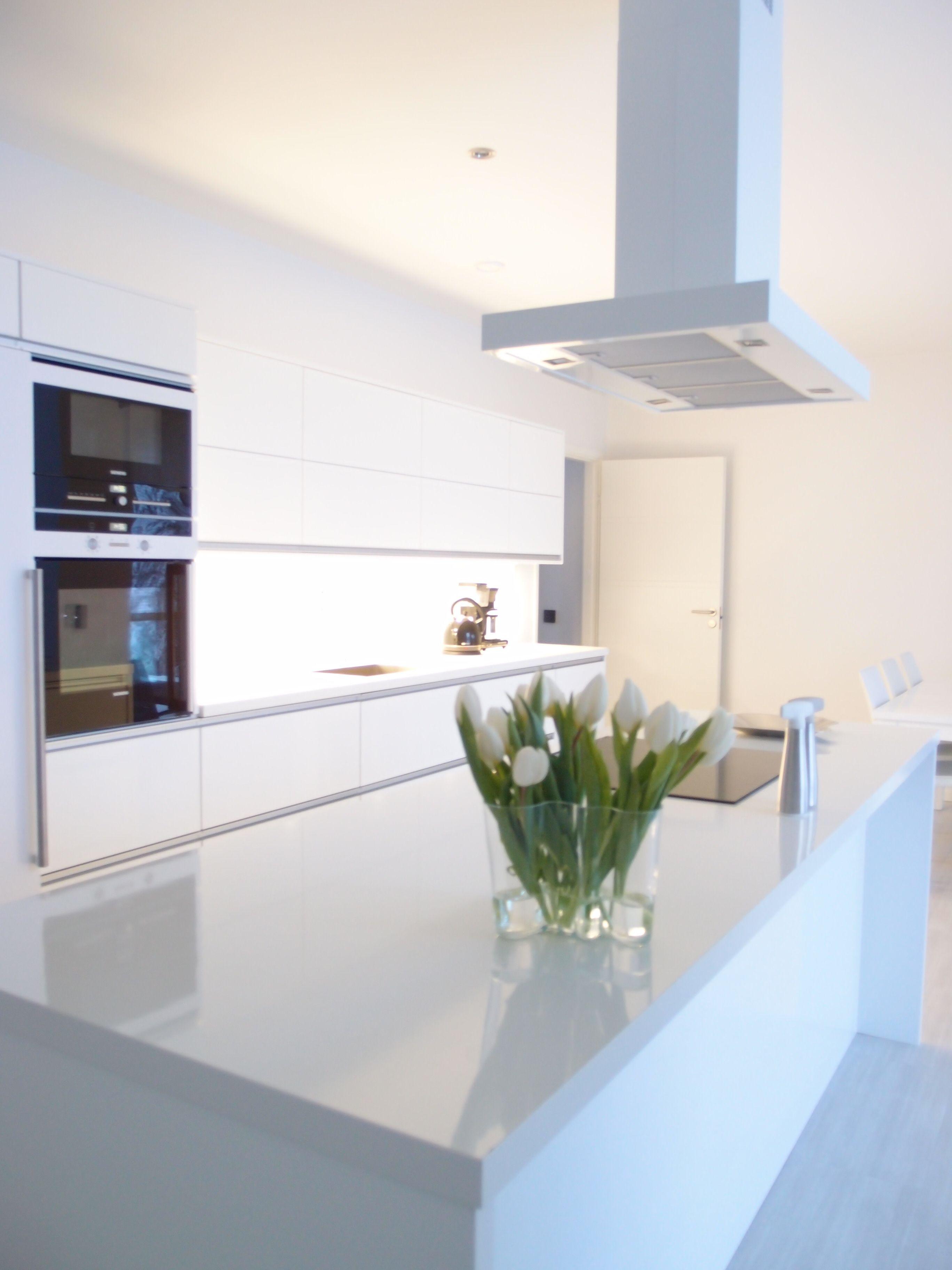 Modernia kiiltävää ja valkoista. Tämän keittiön minimalistinen ilme soveltuu hyvin avokeittiöön.