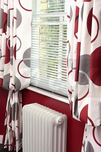 Image Close Up Of White Slatted Blind And Red Patterned Curtains