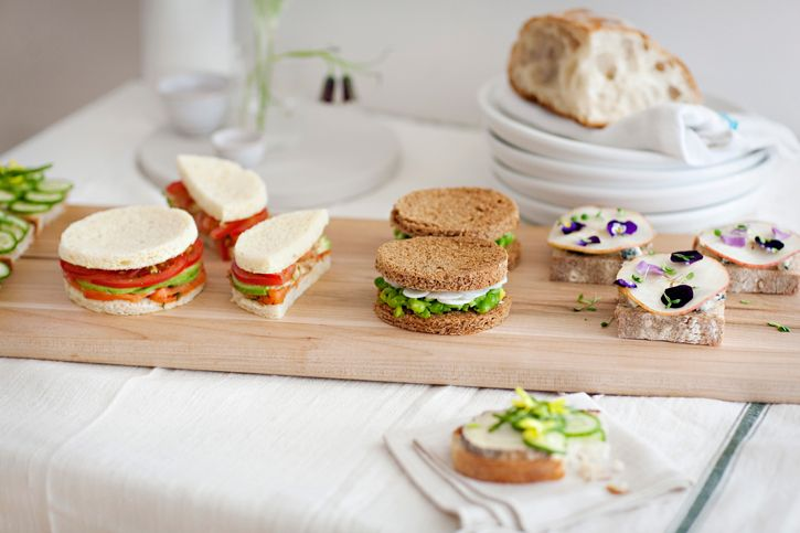Afternoon Tea Sandwiches.   Pea mash with Mint, White Radish, Olive oil, and Black Sea Salt on Rye Bread (egg shape)  - Blue Cheese, Pear, Violas on Mixed Grain (open faced Square)  - Tomato, Avocado, Salmon, on Brioche (circle shape)  - Cucumber, Goat Cheese, Sea Beans, and Flowering Broccoli  on rustic white (open-faced organic loaf shape)