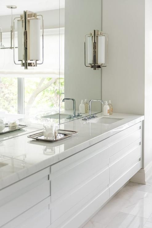 Keeley Tall Pivoting Sconces Are Mounted On Frameless Vanity