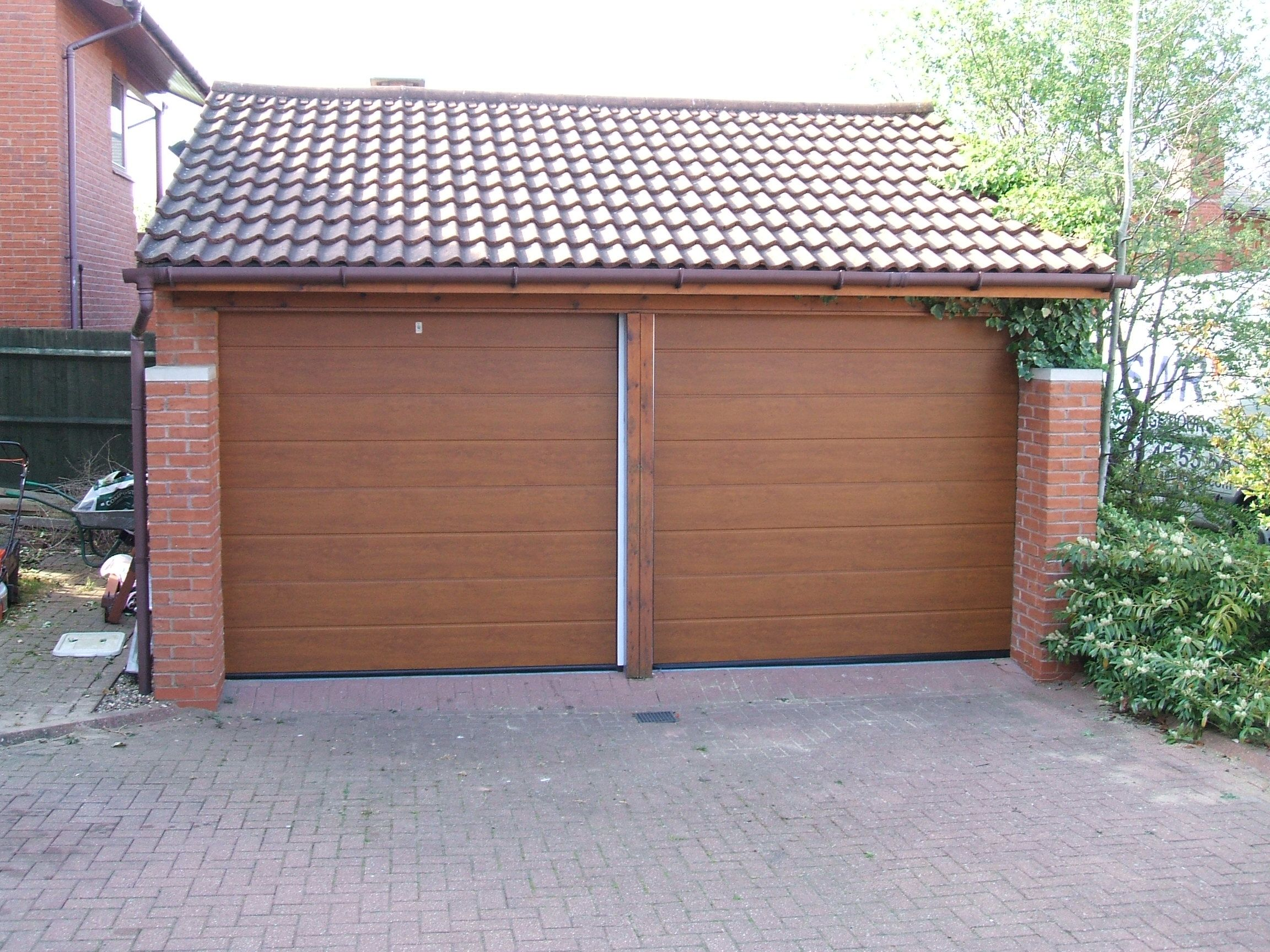 Doors and sidelights matching window on front and black onduline roof - Hormann M Ribbedsectional Decograin Garage Door