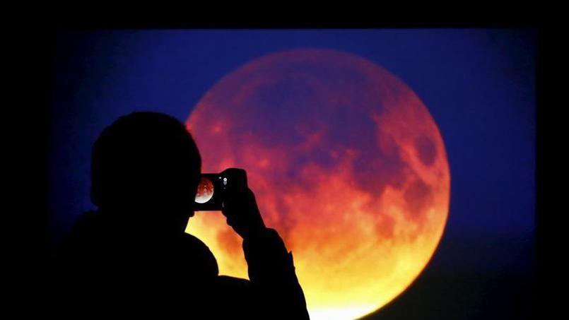 Un homme prend une photo de la lune à Varsovie en Pologne.