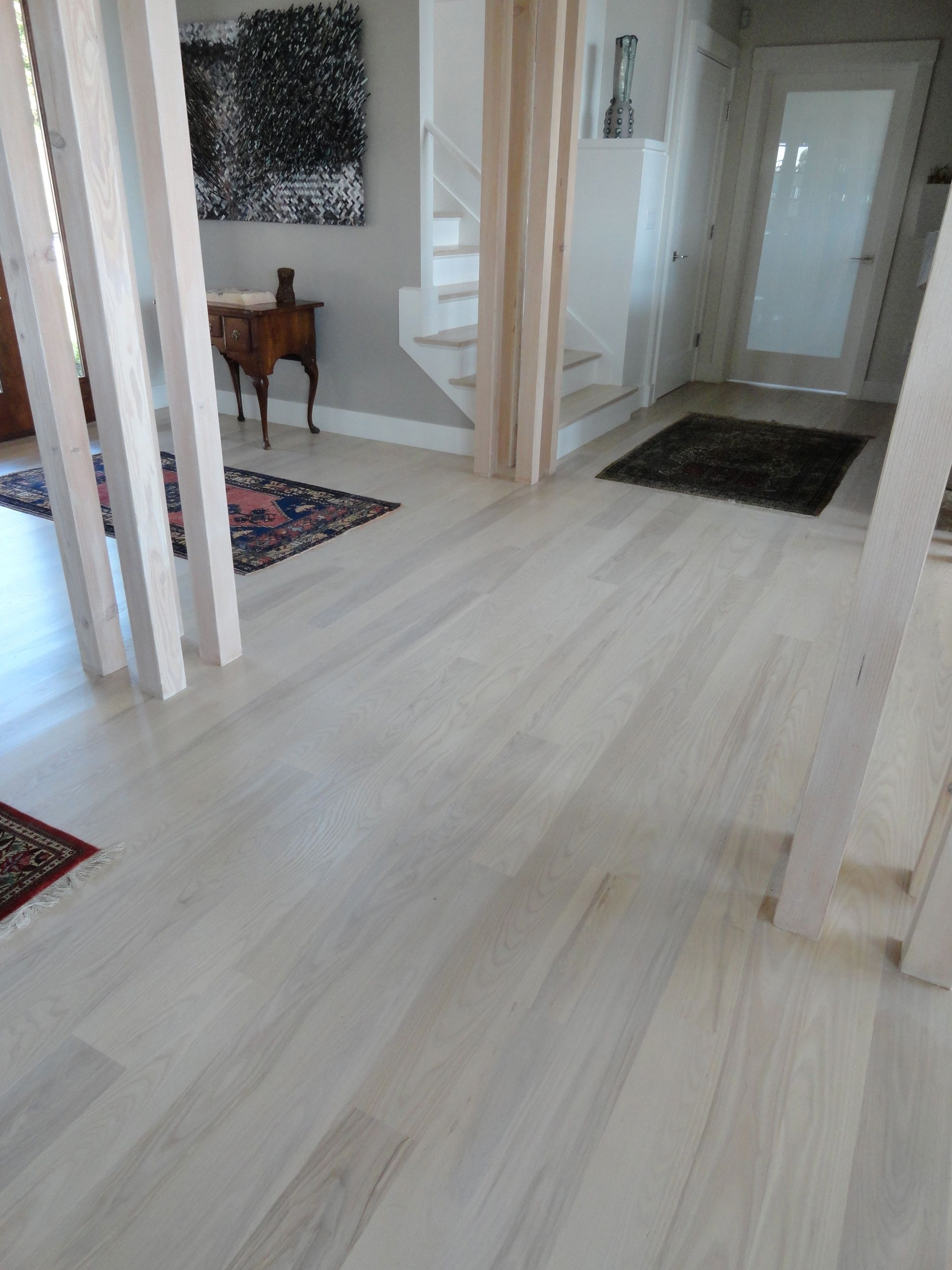 elegant laminate grey wood floors with white wooden pillars as well as single frosted main door - Grey Hardwood Floors