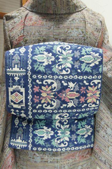 スモークがかった深く美しいブルーの地に、パウダーカラーで織り出された東欧の刺繍ファブリックを思わせる装飾模様が愛らしい名古屋帯です。