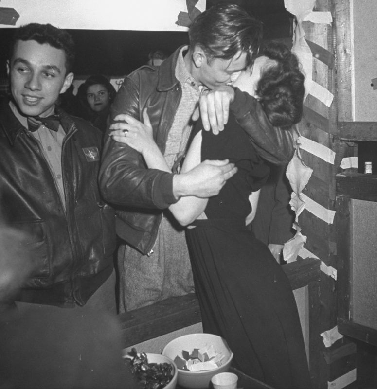 A couple kissing at a kissing booth during a fair at the University of Wisconsin. 1946.