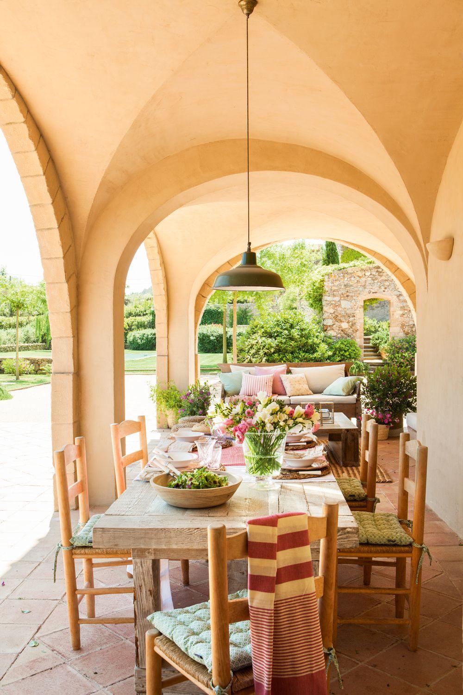 00433883. Comedor exterior bajo porche con arcos, con mesa de madera y sillas rústicas con cojines sobre el asiento_433883