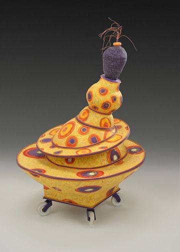 Jo Stealey. | Yellow form with wheels. Purple coiled element at top. Lid removes to reveal netted vessel inside. Materials: Cast paper, reed, waxed linen, porcelain wheels