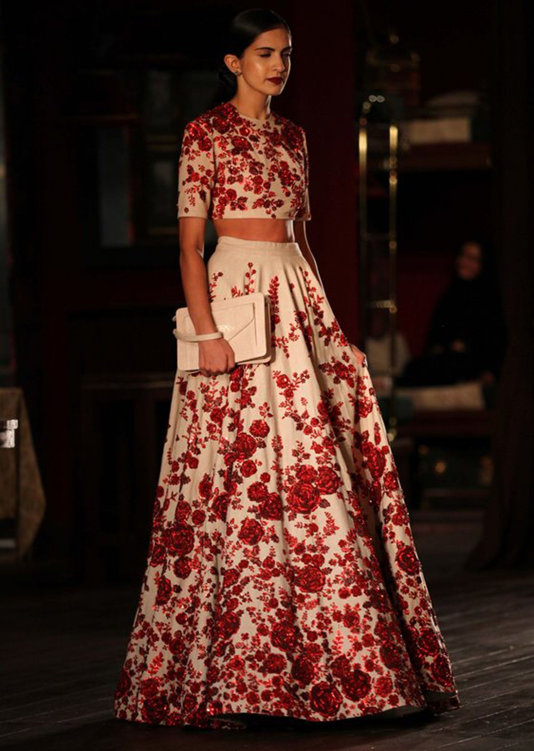 Model walking the ramp with red and white floral gown for for Indian women wedding dress