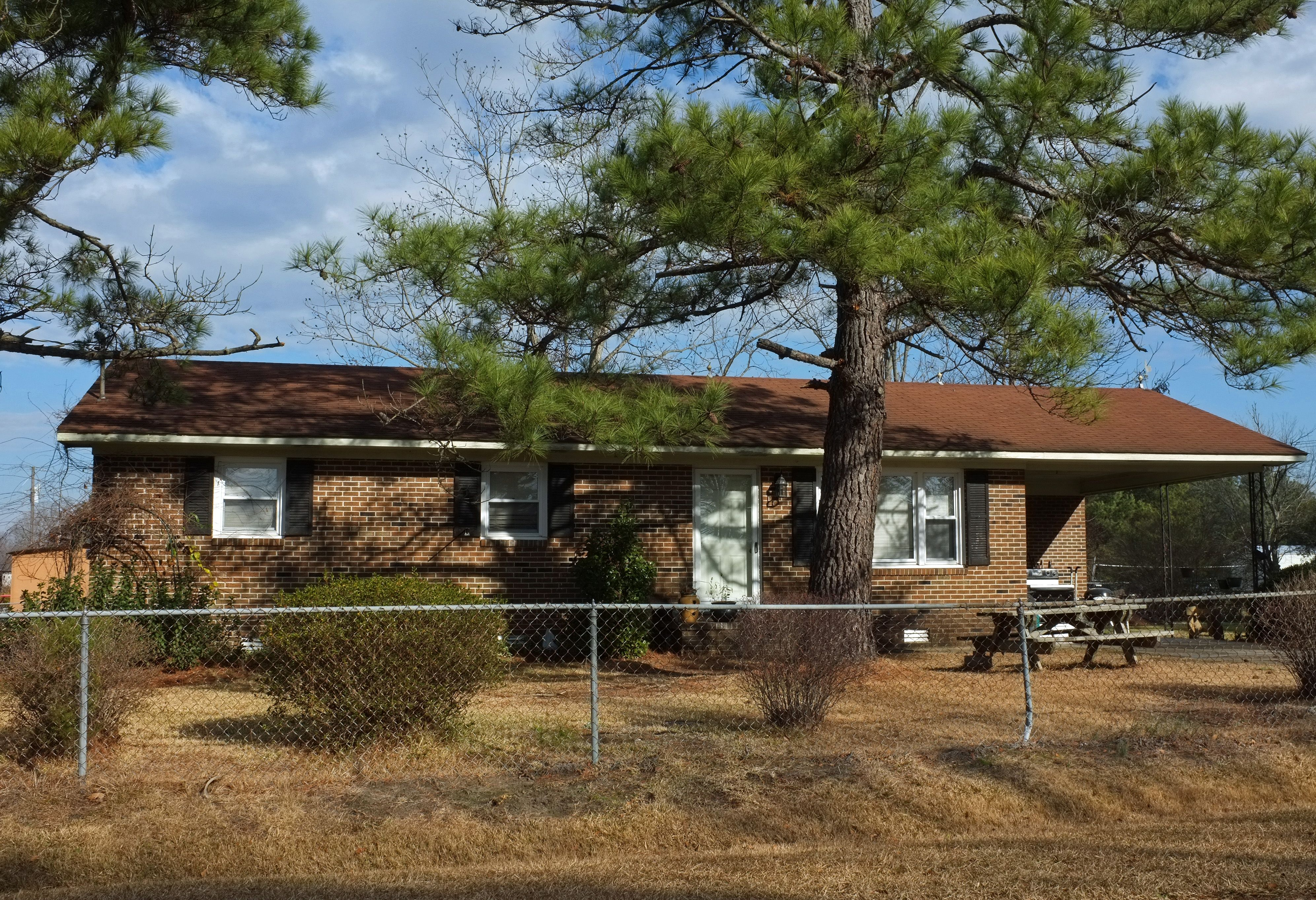 Brick Ranch Style Home With Carport Under Pine Trees