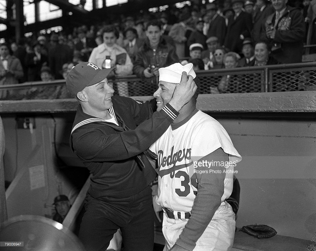 Brooklyn Dodgers pitcher Johnny Podres places a sailor hat on the head of teammate Roy Campanella before a game at Ebbets Field in Brooklyn, New York.