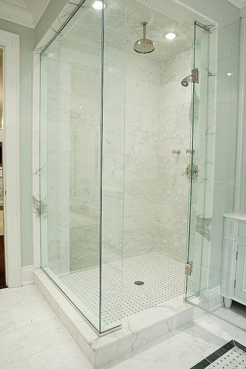 Stunning bathroom with blue gray walls framing a frameless glass corner shower with rainfall - Glass shower head ...