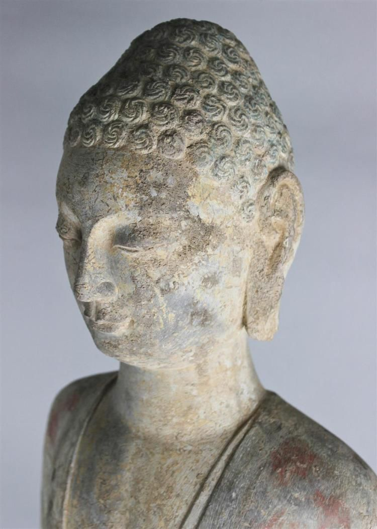 <b>PAINTED STONE FIGURE OF THE BUDDHA, NORTHERN WEI DYNASTY</b> the deity standing with arms (missing) presumably at his sides, with downcast gaze and his hair in tight curls, his robes picked out in polychrome, with black base - h:35.75 in.