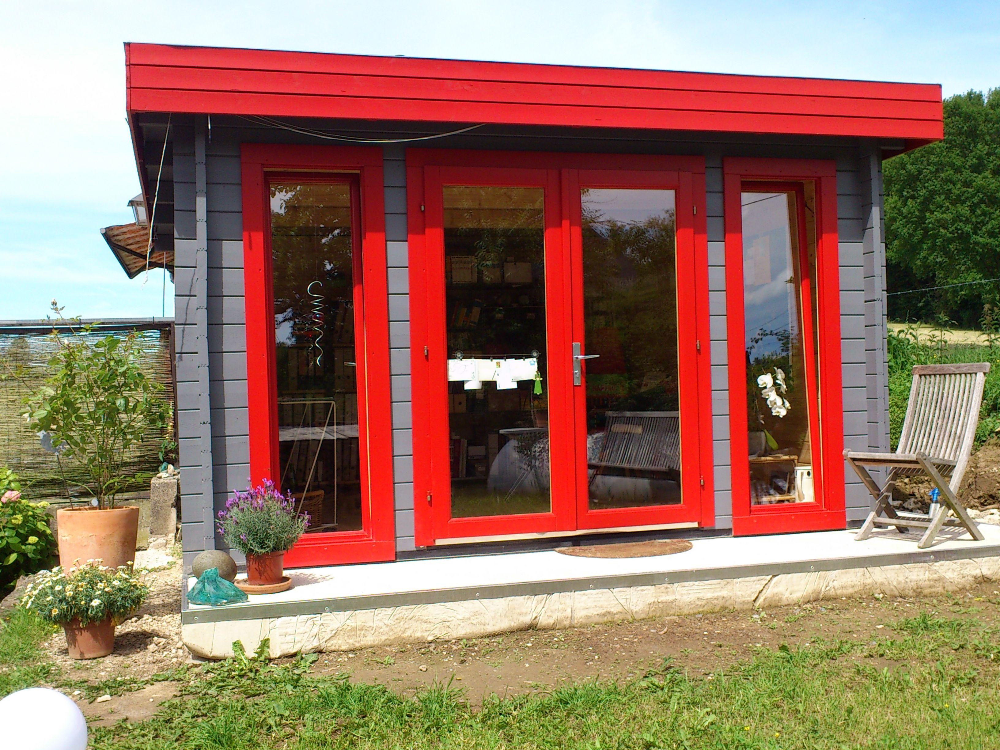 Modernes Flachdach Gartenhaus. Der Anstrich in leuchtendem Rot und