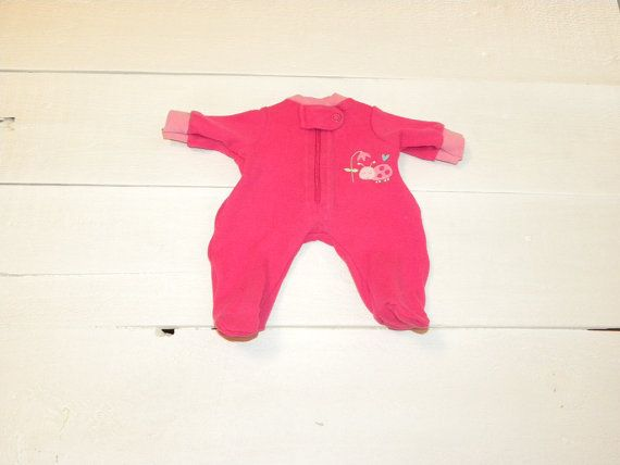 A hot pink pair of footed sleepers for the 12 inch baby doll. The front opens with a zipper and has a tab and snap at the neck. There is pink ribbing