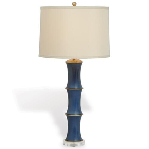 """Modern classic with accents of solid brass and navy porcelain. Acylic base. Rivoli collection also includes candleholders. 150 Watts max, 3-way switch Shade: 15""""x16""""x11"""" Honey Beige polyester/round hardback shade. Single fold self trim. Brass spider."""