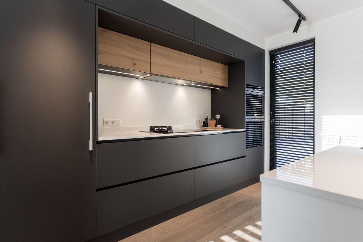 Mat zwarte keuken gecombineerd met hout een wit eiland. dun wit