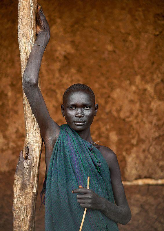 Suri boy with clay stripes painted on his torso, Omo Delta