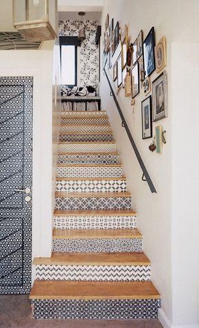 Le papier peint noir et blanc à différents motifs permet de relooker l'escalier et le palier. Une galerie tableau aux tons assortis de noir, blanc et bois blond décore le mur en suivant la rampe.