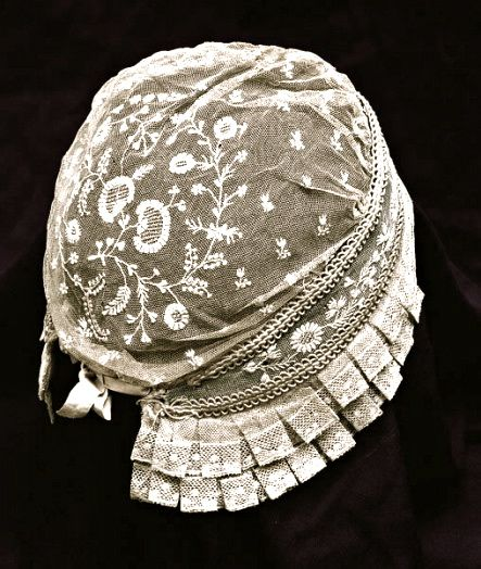 beautiful example of an antique Brussels lace baby bonnet from vintagetextile.com