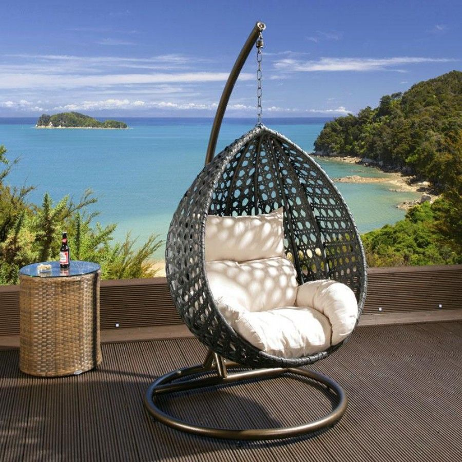 Black rattan hanging chair with cream cushion covers.
