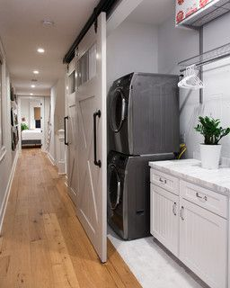 Love the sliding barn doors, distressed pine floors, clean white cabinets, and silver appliances. #laundryrooms