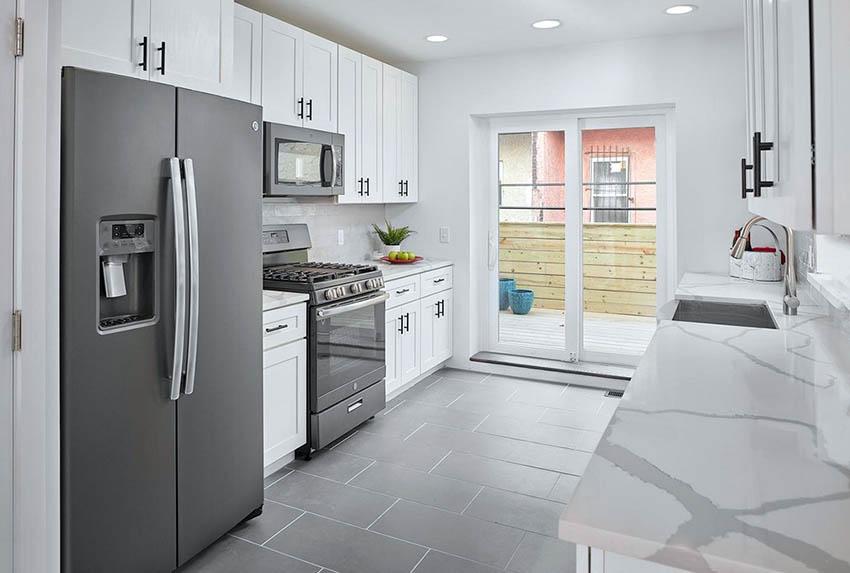 27 Stylish Modern Galley Kitchens (Design Ideas) #whitegalleykitchens Modern galley kitchen with white quartz countertops, white cabinets and sliding glass door #whitegalleykitchens