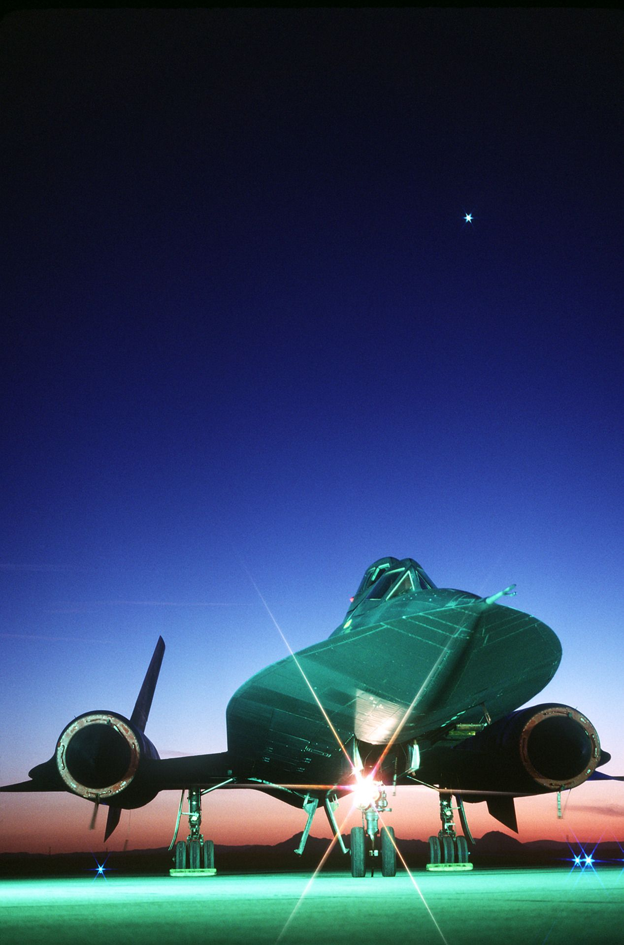 A front view of an SR-71B Blackbird strategic reconnaissance training aircraft on the runway at sundown. Photo: TSGT Michael Haggerty. Location: BEALE AIR FORCE BASE. Date Shot: 6/1/1988.